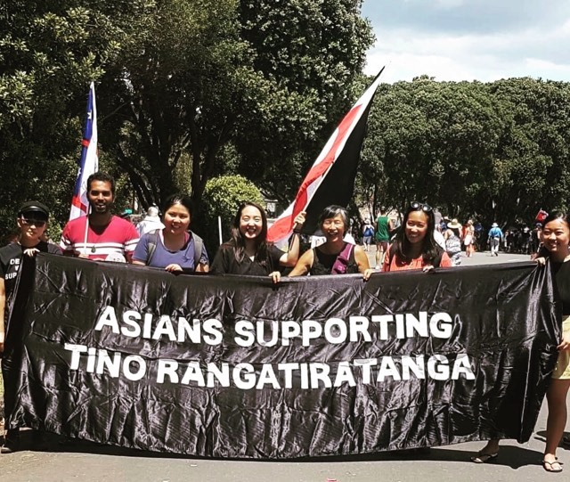 """Photo of a group of Asian people smiling and standing behind a banner reading: """"Asians Supporting Tino Rangatatiratanga."""""""