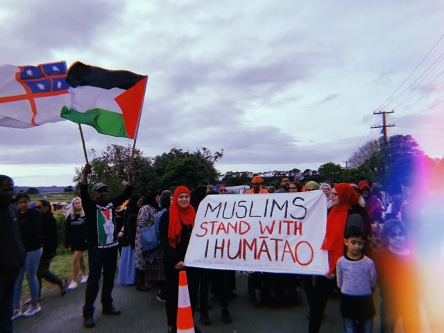 """Photo of a group of Muslims visiting the protest site Ihumātao. There are women holding a banner smiling, with children at the front. The banner reads: """"Muslims Stand With Ihumātao."""""""